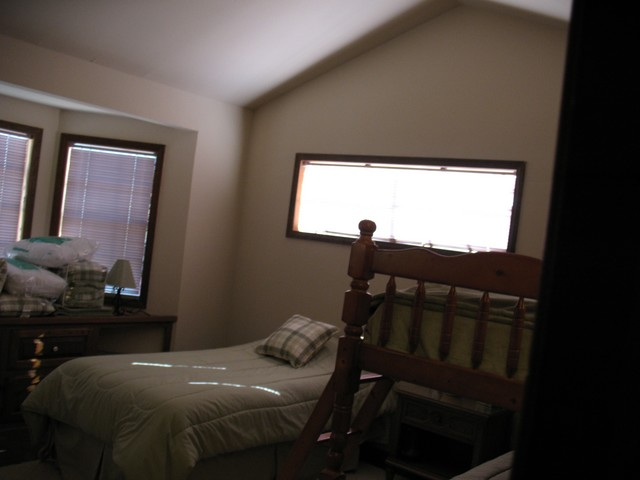 This is the light green bunk bedroom that has a twin bed and a twin bunk bed. It is located at the end of the hall on the left.