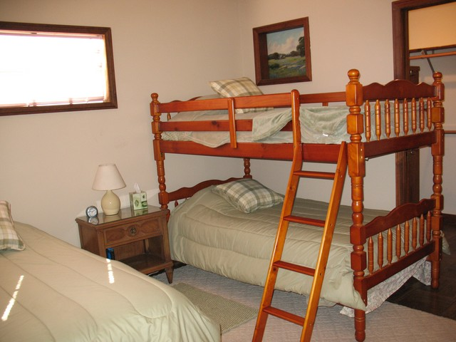 Behind the bunk beds in the light green room, is a large walk in closet.