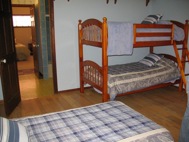 This is the blue bunk bedroom located off the main hallway. Take the second door on the left. you can see the light green bunk bedroom and full bathroom through the doorway. This bedroon also has a walk in closet.