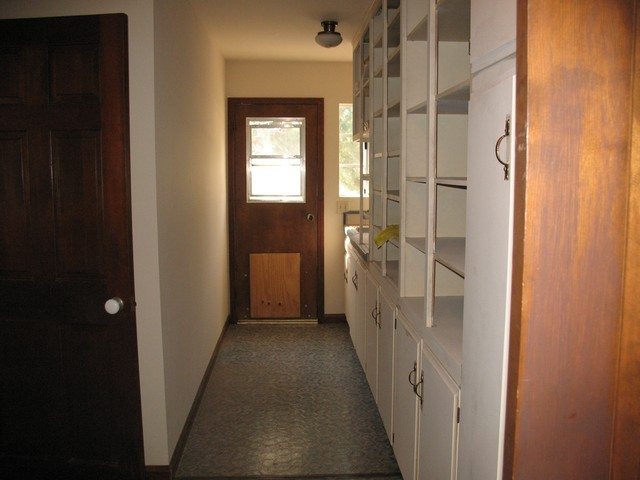 looking down the hallway toward the back of the house behind the kitchen, on the right is plenty of storage space and the cupboards and closet are filled with all cleaning supplies needed including broom and vacuum. The door to the left leads to the master bedroom and master bathroom.