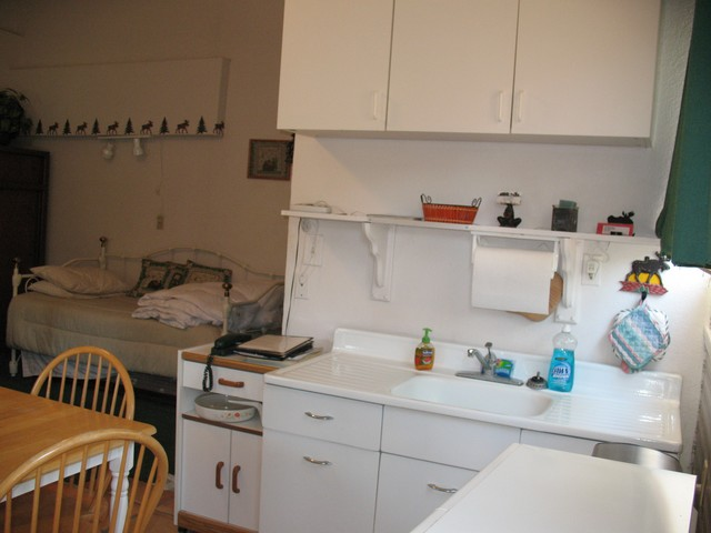 Here you can see the kitchen area. It has cooking and eating equipment, a refrigerator, microwave oven and dining area. In the background you can see the twin trundle day bed that sleeps two.