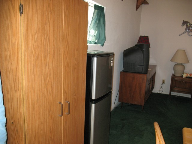 It has a large color TV and a dresser for clothing. In addition, it has a standing pantry for non parishable foods next to the refrigerator/freezer.